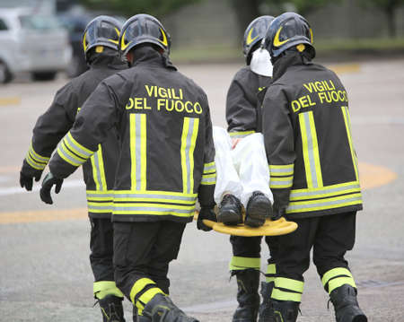 Italian firefighter team uniform with firefighters writing while helping the wounded with the stretcher after a tragic road accident