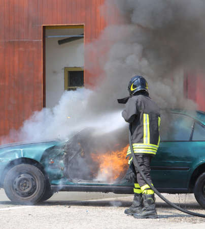 intervening: broken car with flames and black smoke and firefighter intervening to tamper with the fire Stock Photo