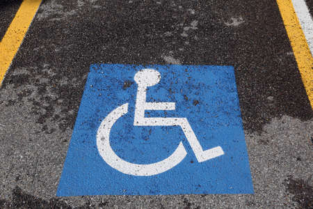 wheelchair symbol on blue background in the reserved parking for disabled people