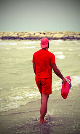 Muscular barefoot lifeguard with red uniform controls the coast during the marshal