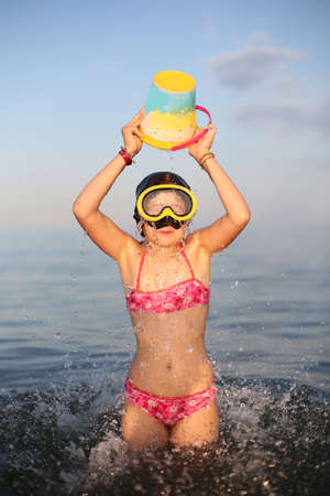 Pretty little girl in swimsuit plays with bucket full of water at sea