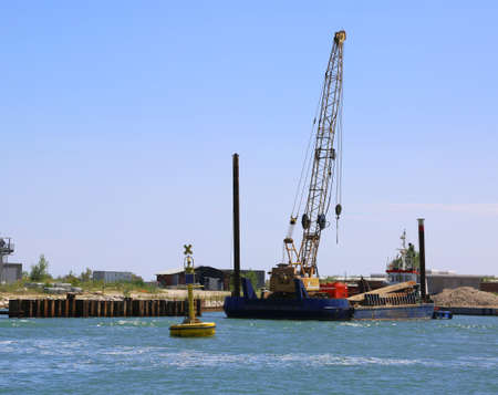Giant cranes at a shipyard for the construction of a dam on the sea Stock Photo - 83154666