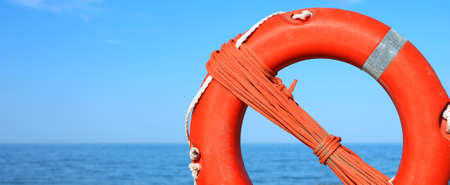 Orange life buoy for the rescue of personsand the sea on background Stock Photo