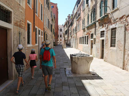 Family walks through the narrow street of venice called CALLE and an ancient well Stock Photo