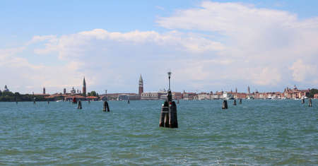 Skyline of Venice island in Italy by boat in the middle of the sea. You can see the high bell tower of St. Marks Basilica