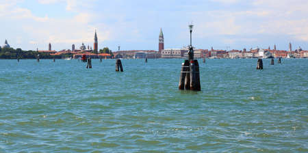 Skyline of Venice island in Italy by boat in the middle of the sea. You can see the high bell tower of Saint Mark Stock Photo