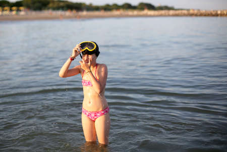 Little girl in swimsuit with diving mask while playing on sea water