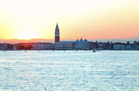 Sun at SUNSET in VENICE in Italy and the Campanile of Saint Mark photographed by the canal of GIUDECCA Stock Photo