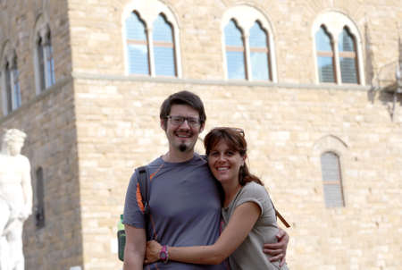 Happy young couple in honeymoon in the art city of FLORENCE in Italy and in the background the ancient palace called Palazzo Vecchio Stock Photo