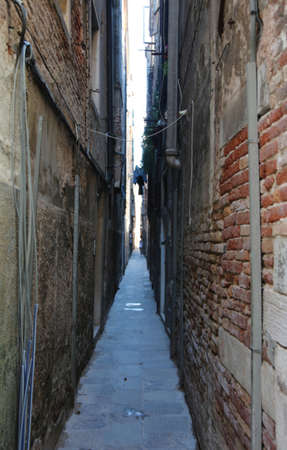 Narrow street with the walls of homes almost touching and the sky just visible