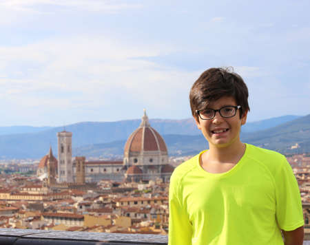 Smiling boy in the city of FLORENCE in Italy with yellow t-shirt and the Ancient Dome in Background