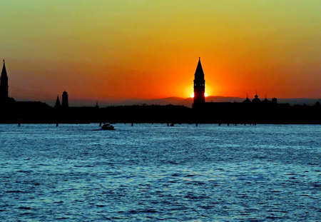 Orange Big Sun at SUNSET in VENICE in Italy and the Campanile of Saint Mark