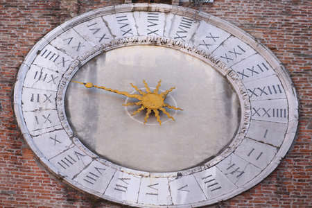Ancient clock with one hand to measure the hours and Roman numerals on the clock dial on the island of Venice in Italy Stock Photo