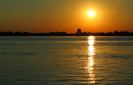 Yellow sun at the SUNSET with reflections on the water of the Adriatic Sea near the island of VENICE in Italy
