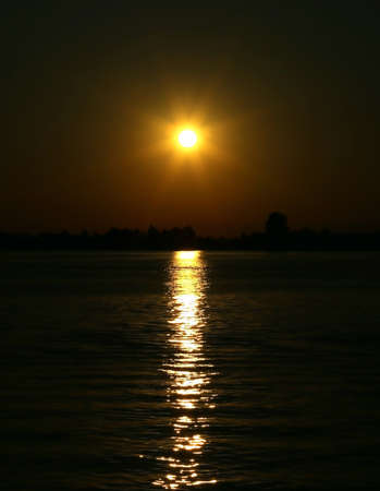 Yellow Big sun at the SUNSET with reflections on the water of the Adriatic Sea near the island of VENICE in Italy
