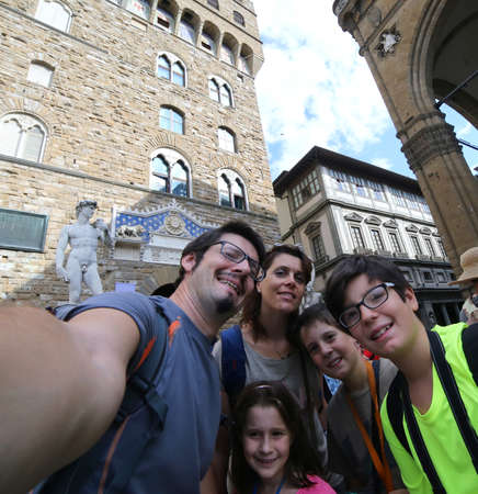 Happy family with five people and 3 children traveling to FLORENCE in italy  and the Old Palace in background