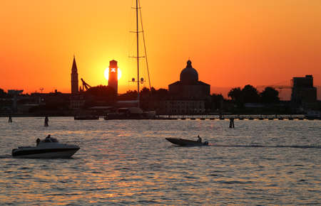 Great sun at sunset in VENICE in Italy and the shape of the churches and bell towers of the most famous island of Europe