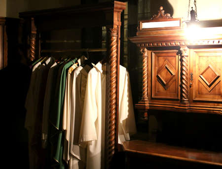 Many cassock for dressing priests in the sacristy of an ancient Christian church Stock Photo