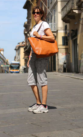 Elegant young woman walks through the streets of a European city with the big leather bag