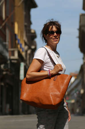 Elegant young woman walks through the streets of a city with the big leather bag Stock Photo