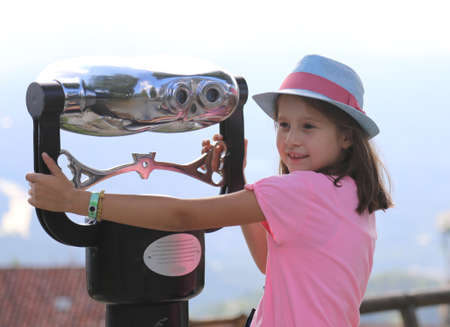 Little Girl with hat and pink t-shirt and binoculars to watch the city