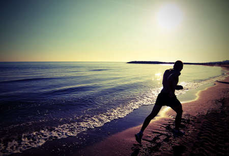 Man runs very fast on the beach at dawn in backlight with lomo photograph effect