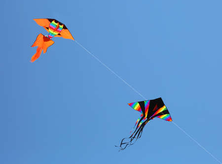 Two big kites fly high in the blue sky Stock Photo