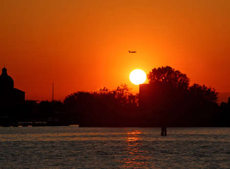 Big Red sun at sunset and a plane high in orange sky Stock Photo