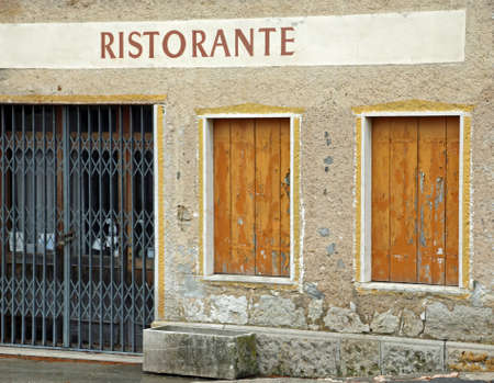 big sign with the italian Text RISTORANTE thah means Restaurant with the gate closed because of the economic crisis