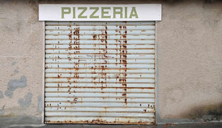 Huge sign with the italian Text PIZZERIA  with the closed rusty gate because of the economic crisis