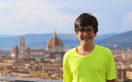 Smiling boy with long hair and the background of the city of FLORENCE in Italy Stock Photo