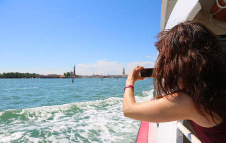 young woman takes picture of Venice in Italy from the boat