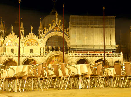 Venice in Italy by night Basilica of Saint Mark and tables with chairs in the main square Stock Photo