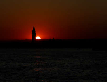 Sun at SUNSET in VENICE in Italy and the Campanile of Saint Mark Stock Photo