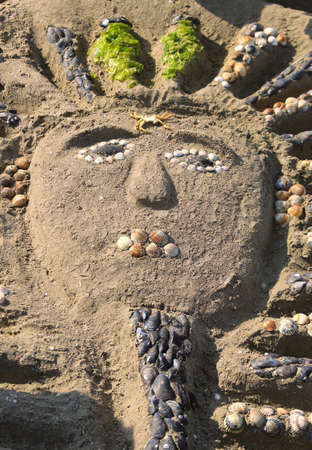 sarcophagus made by children on the beach of the sea with sand and shells Stock Photo