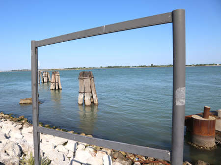 Window frame on Venetian lagoon with poles in the sea to moor the ships