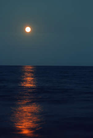 Reflection of a big red full moon on the horizon over the sea in the evening