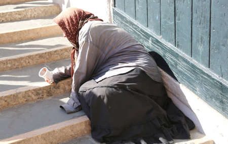 Old gypsy woman with headscarf and long skirt begging people on the large staircase Stock Photo