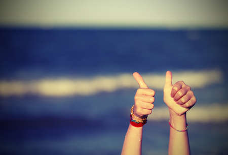 Thumbs up to tell OK and the background of the sea with vintage effect