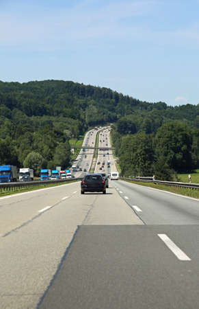Very long highway with three lanes for every direction of traffic with cars and trucks