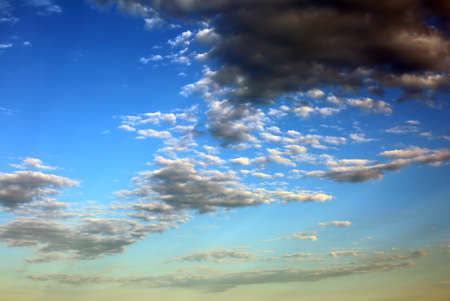 Simple blue sky background with dark clouds at sunset