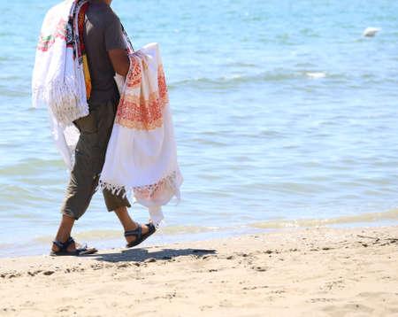 Abusive street vendor with fabrics and fabrics walks on the sunny beach in summer Stock Photo