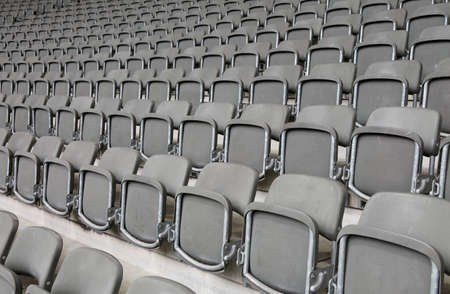 lots of reclining chairs on the stadium bleachers with no people before the sporting event