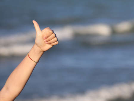 Thumbs up of babys hand to say ok and the background of the sea