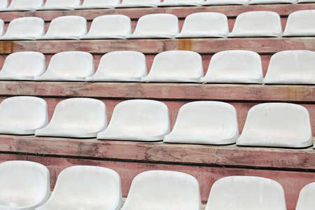 White seats on stadium bleachers with no people before the meeting sports