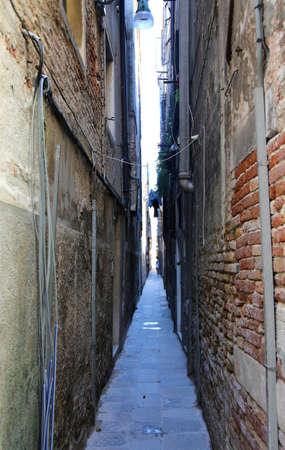 Smalle straat met de muren van huizen bijna aanrakend en de lucht net zichtbaar