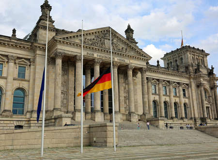 Reichstag building is Parliament of Germany in Berlin with huge flag at half mast. The big dedication text  over the main entrance DEM DEUTSCHEN VOLKE meaning To the German People