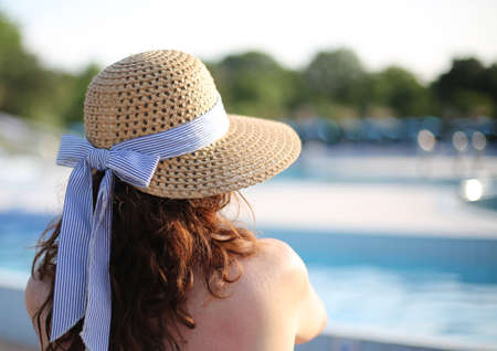 woman with straw hat relaxes in the exclusive luxurious spa on the edge of the pool Stock Photo - 85050271