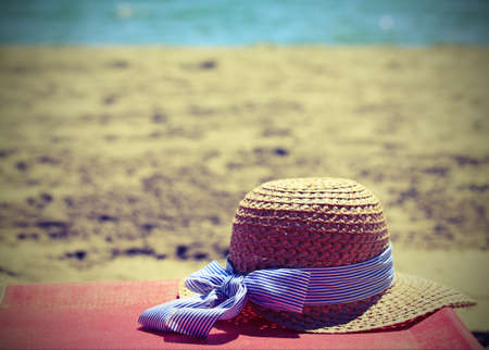 straw hat on the beach near the ocean in summer with vintage effect Stock Photo