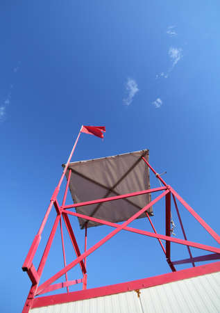 high turret of lifeguard on the beach with the red flag and blue sky